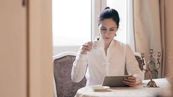 Woman using tablet and drinking coffee by table video