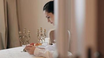 Mujer con tableta y tomando café por mesa video