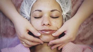 Mujer afroamericana recibiendo masaje facial en el salón de spa video
