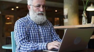 adulto sênior homem sentado com um laptop sorri afavelmente. video