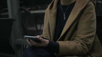 junges Mädchen sitzt auf einem Stuhl und hält ein Handy