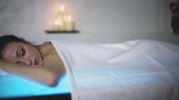 Mujer joven recibiendo masaje con piedras calientes en el salón spa video