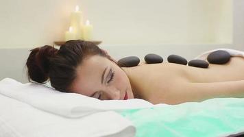 Mujer en el salón de spa con piedras calientes video