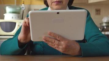 una mujer mayor con gafas está usando una tableta video