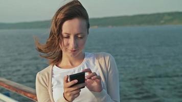 Frau mit Handy auf Deck des Kreuzfahrtschiffes