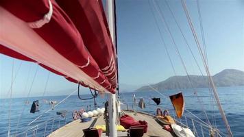 no convés de um veleiro. montanhas na parte de trás. video