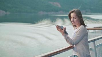 Mujer con tableta en la cubierta del crucero al amanecer. video