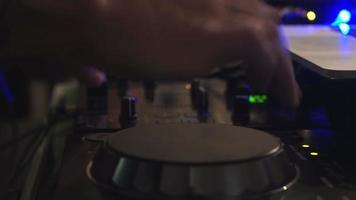 Dj hands on equipment deck and mixer with record at cafe video