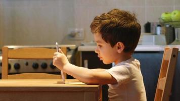 SIDE VIEW: A cute little child uses a tablet PC at a table