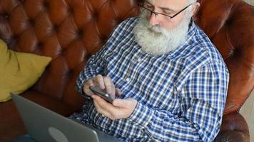 un professeur âgé tape un message sur un smartphone
