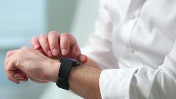 um homem de camisa branca usa um relógio inteligente. fechar-se.