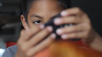 Junge, der Spaß mit Spiel im Smartphone hat