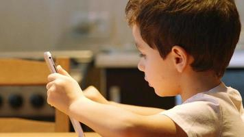 PORTRAIT: A cute little child uses a tablet PC at a table