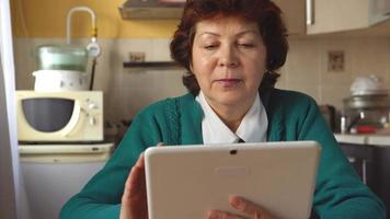 una donna matura sta usando un tablet pc a casa