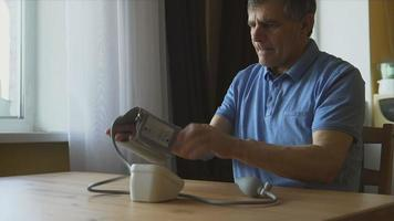 Elderly man measuring the blood pressure at home video