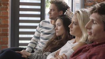grupo de jovens amigos juntos assistindo televisão no sofá. video