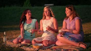 Three young women having a picnic together at sunset