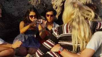 grupo de jovens tirando fotos juntos na praia