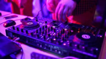 DJ riscando no convés de uma discoteca