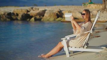 Woman with pad making photos of sea sitting in deck chair on beach video