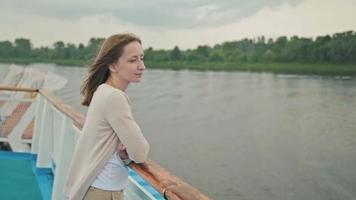 joven y bella mujer de pie en la cubierta del crucero y mirando el río. video