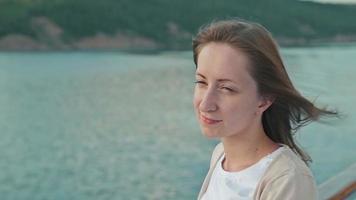 jovem mulher bonita em pé no convés do navio de cruzeiro e olhando para o rio.