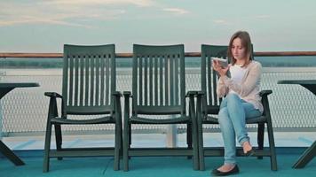 Mujer con tableta digital pc sentado en la cubierta del crucero al amanecer. video