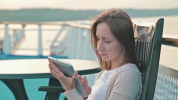 mulher com tablet digital pc sentada no convés de um navio de cruzeiro ao nascer do sol