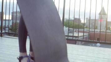 femme roule puis déploie un tapis de yoga, sur le toit-terrasse le matin