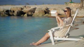 Femme avec pad faire des photos de mer assis dans la chaise longue sur la plage