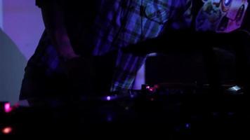 DJ rabiscando discos de vinil e mixando nos decks de uma discoteca em uma boate