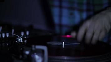 DJ grattant des disques vinyles et mixant sur les platines dans une discothèque en discothèque