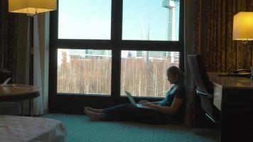 Frau uisng Laptop durch das Fenster im Hotelzimmer
