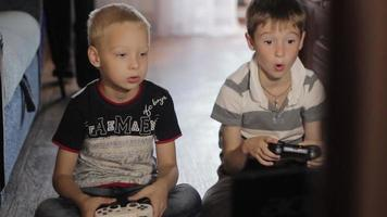 two boys playing computer games sitting  at home video