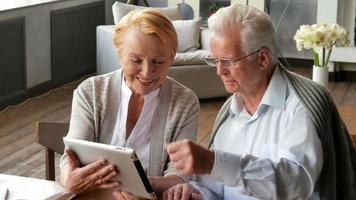 Senior couple websurfing on internet with tablet. Happy elderly man and woman using tablet computer