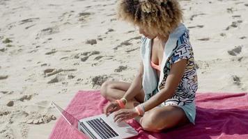 donna con il portatile sulla spiaggia estiva