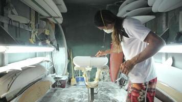 fabricación de tablas de surf, el moldeador lija la tabla de surf con un bloque de lijado