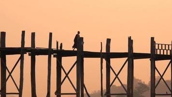 Monje budista caminando sobre el puente U Bein al amanecer, Mandalay, Myanmar (Birmania)