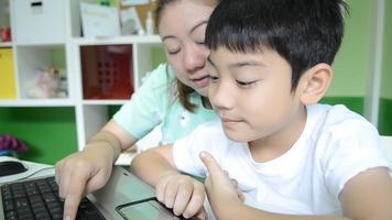 Happy Asian Mom is teaching her son Using Laptop
