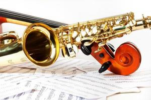 Cello tuning pegs and shiny golden alto saxophone