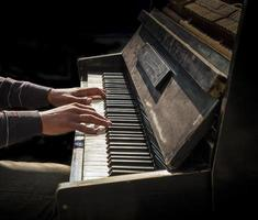 Hands of man playing an old piano photo