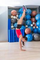 handstand woman workout at gym and swiss balls