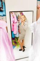 Little girl try on dress in fitting room