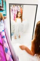 Beautiful little girl try dress before the mirror photo