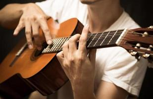 musician plays acoustic, classical guitar