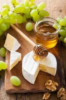 camembert cheese with grapes, honey and nuts on wooden backgroun photo