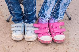 Close-up two pairs of childrens feet dressed in jeans sneakers