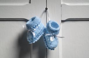 Botitas de bebé azul colgando de la puerta blanca foto