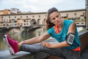 Mujer fitness estiramiento cerca de Ponte Vecchio en Florencia, Italia. foto