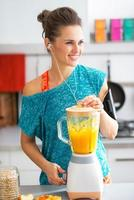 happy fitness young woman making pumpkin smoothie in kitchen photo